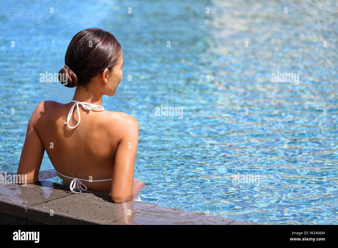 Luxury travel wellness resort bikini woman relaxing in swimming pool. Hydrotherapy spa retreat from behind on side of infinity pool looking away at blue water copyspace. Relaxation vacation concept. - Stock Image