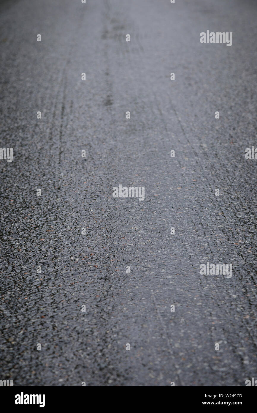 Wet asphalt road on a rainy day. Tilted angle, focused on the foreground. High resolution full frame background. Stock Photo