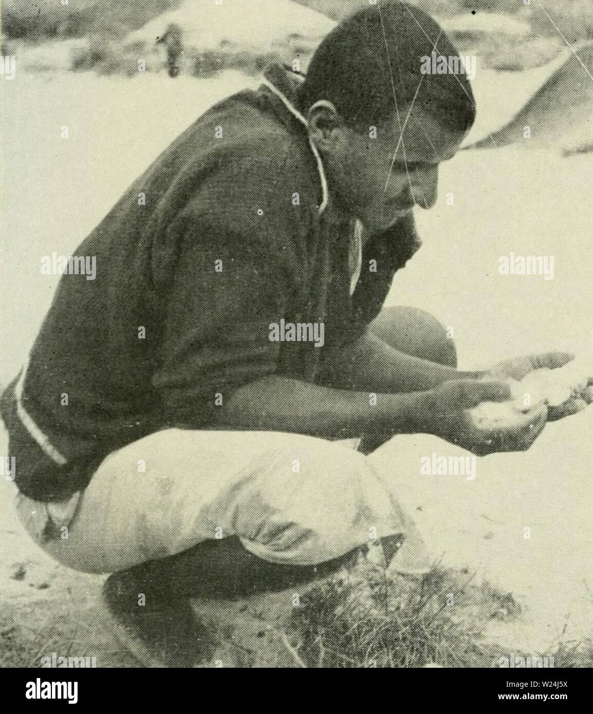Archive image from page 245 of Dahlak with the Italian National. Dahlak: with the Italian National Underwater Expedition in the Red Sea  dahlakwithitalia00rogh Year: 1957  35- This Temenite chief showed us how to dis- cover turtles' eggs hidden under the sand. - Stock Image