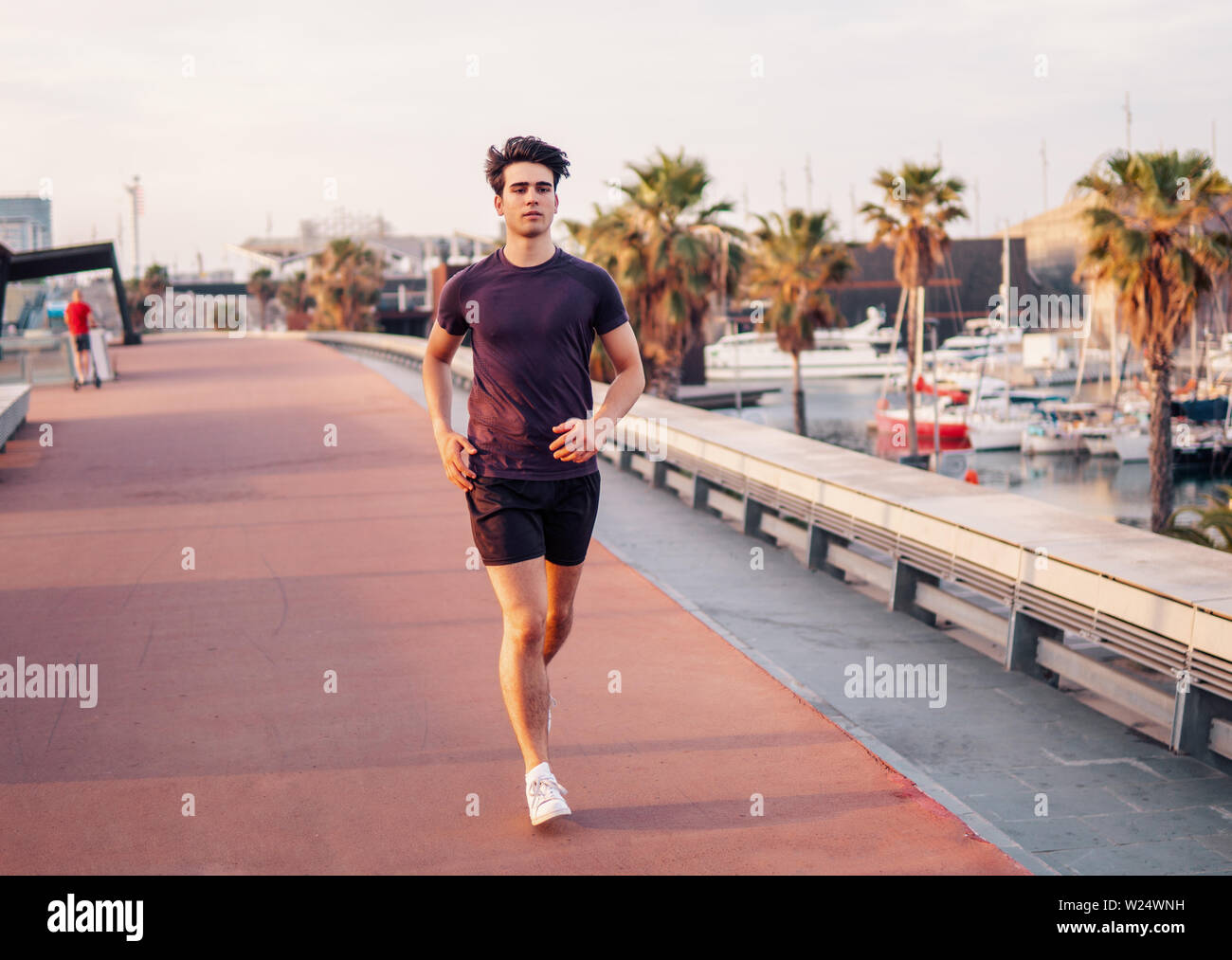 Young athletic man running at park during skyscrapers background Stock Photo