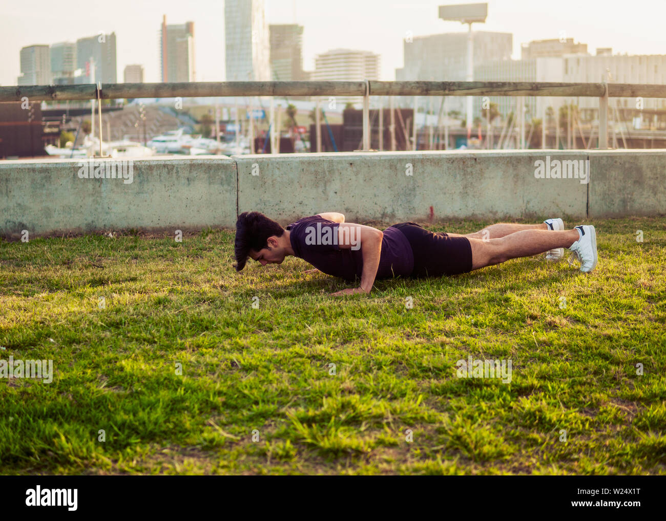 Young athletic man doing pushups exercises at park Stock Photo