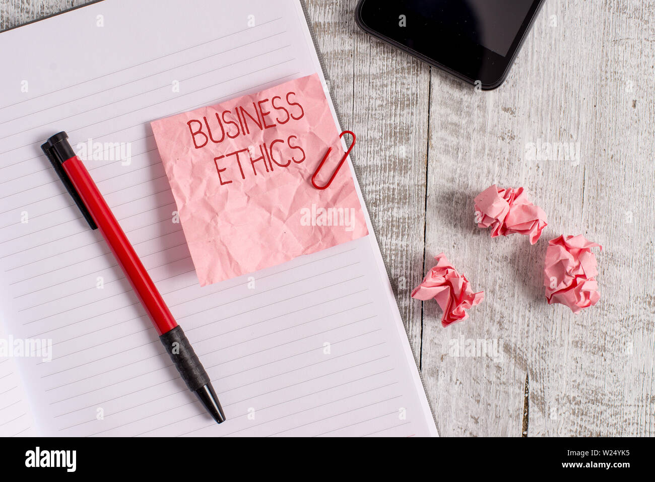 Writing note showing Business Ethics. Business concept for Moral principles that guide the way a business behaves Wrinkle paper notebook and stationar - Stock Image