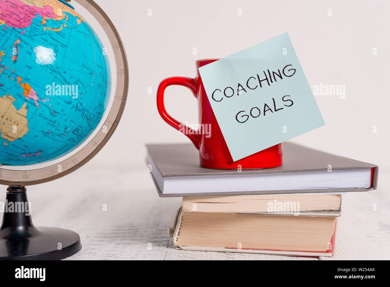 Writing note showing Coaching Goals. Business concept for Empowers individuals Encourages them to take responsibility Globe map world earth cup blank - Stock Image