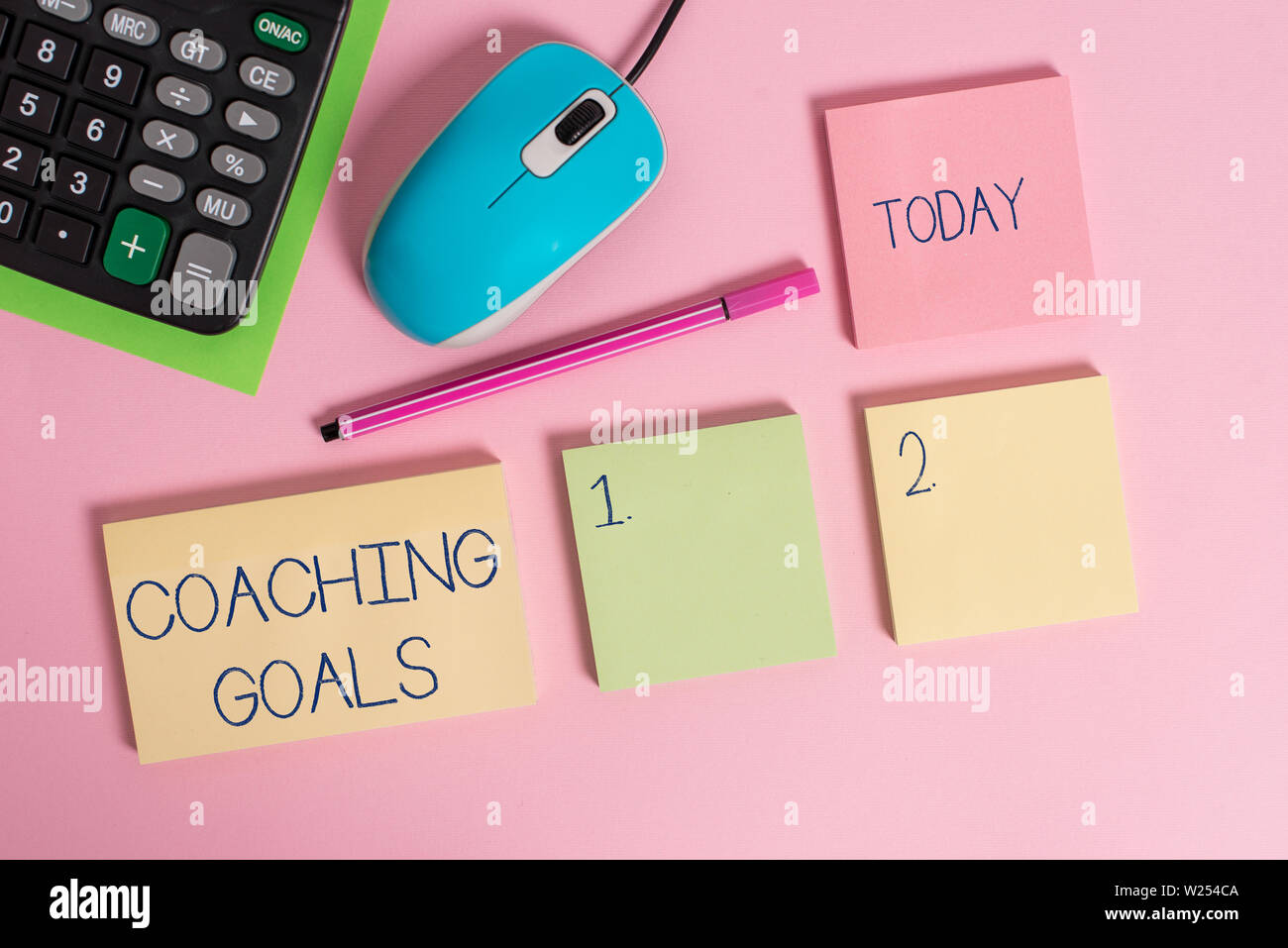 Word writing text Coaching Goals. Business photo showcasing Empowers individuals Encourages them to take responsibility Blank notepads wire mouse calc - Stock Image