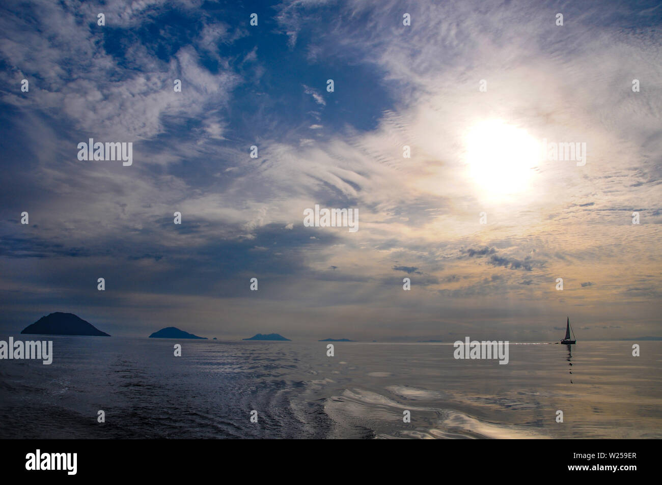 Yacht sailing by the Aeolian Islands, volcanic archipelago, Tyrrhenian Sea, Sicily - at sunrise Stock Photo