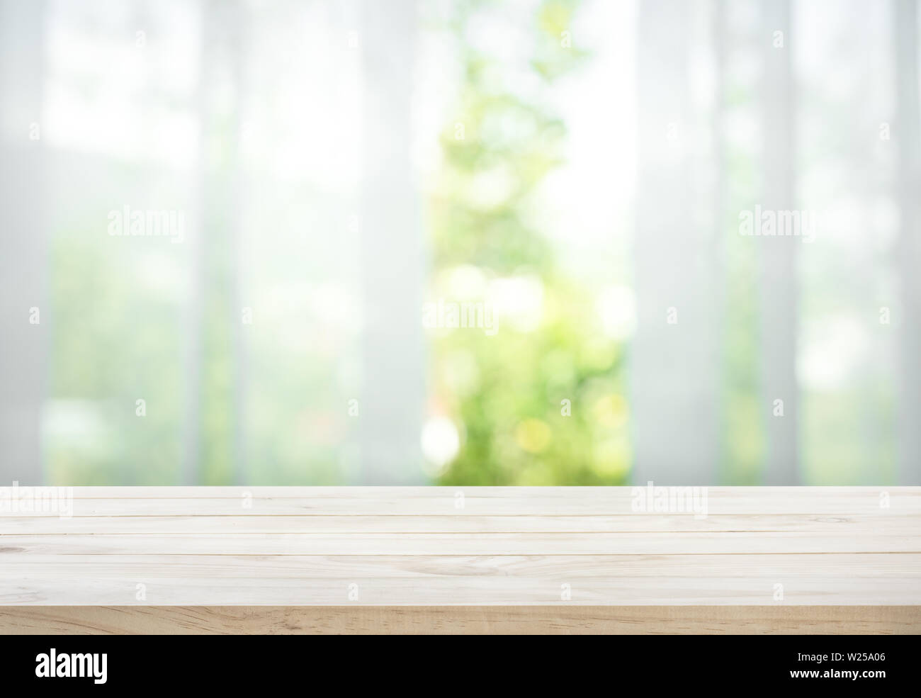 Empty of wood table top on blur of curtain with window view green from tree garden background.For montage product display or design key visual layout Stock Photo