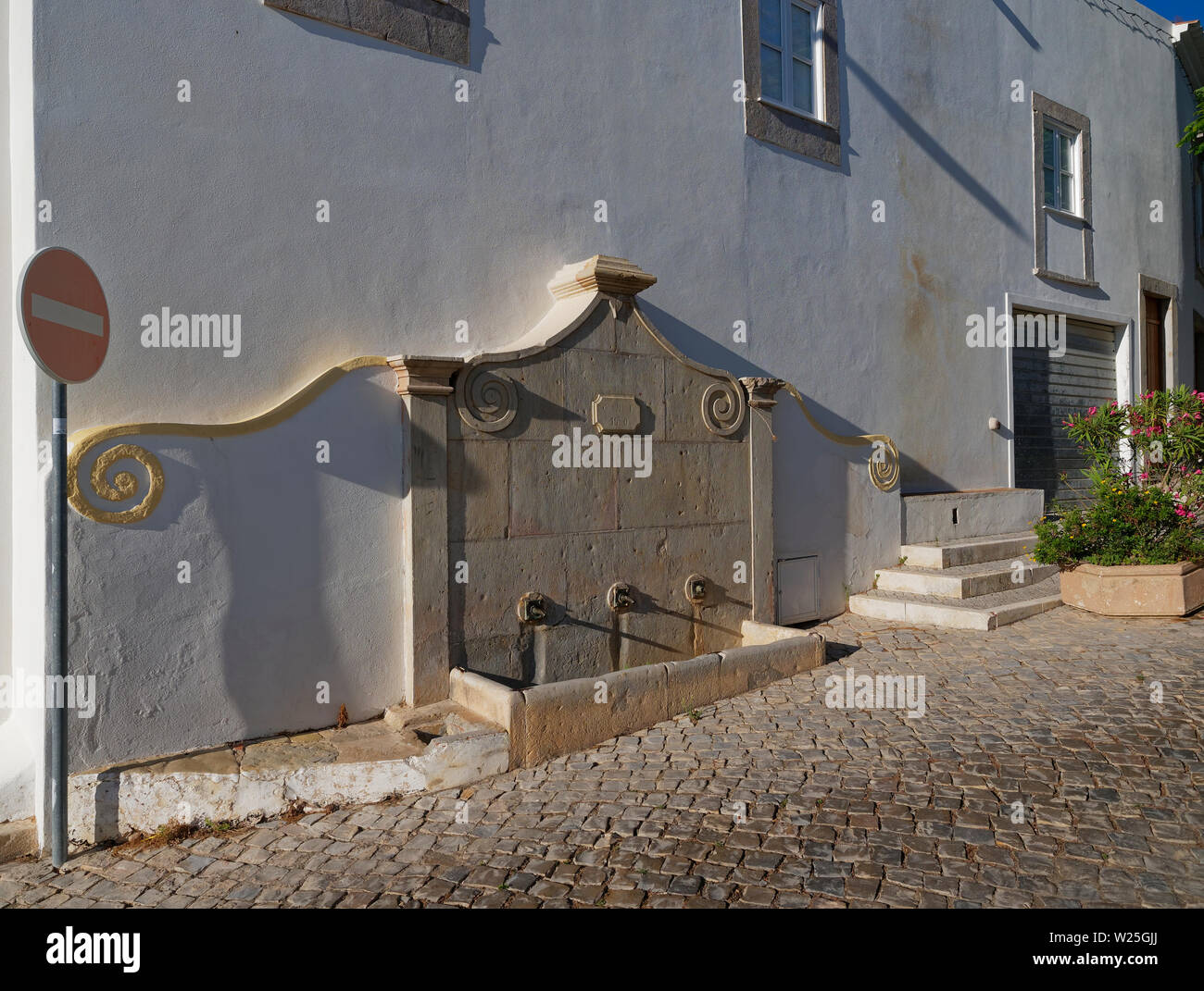 A Three Faucet Town water well in the side of an Old townhouse on a sloping cobbled street in the town of Estoi, near to Faro in the Algarve. Portugal Stock Photo