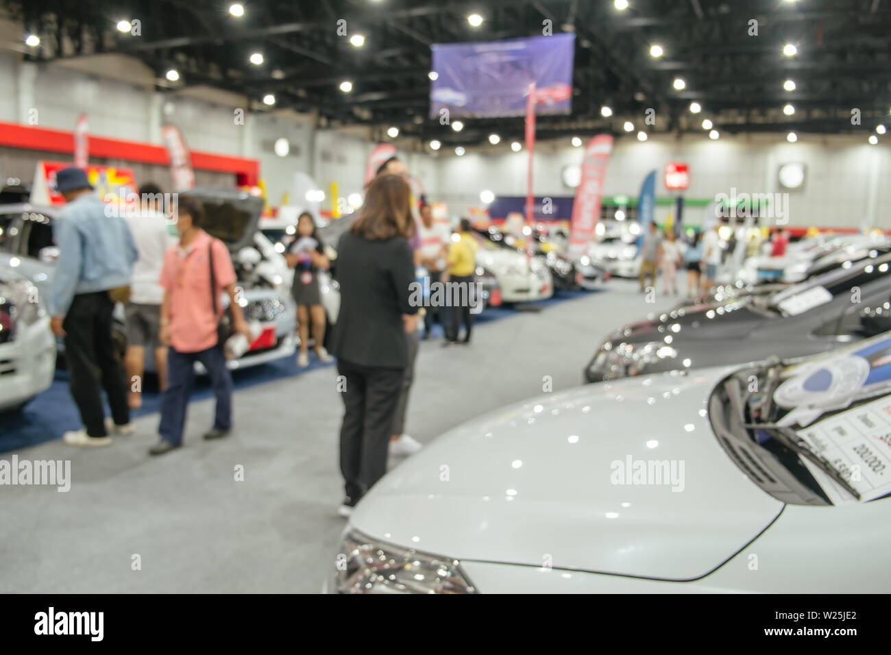 Abstract blurred defocused background of people evaluate and looking for new cars in automobile business commercial event exhibition hall, Thailand. - Stock Image
