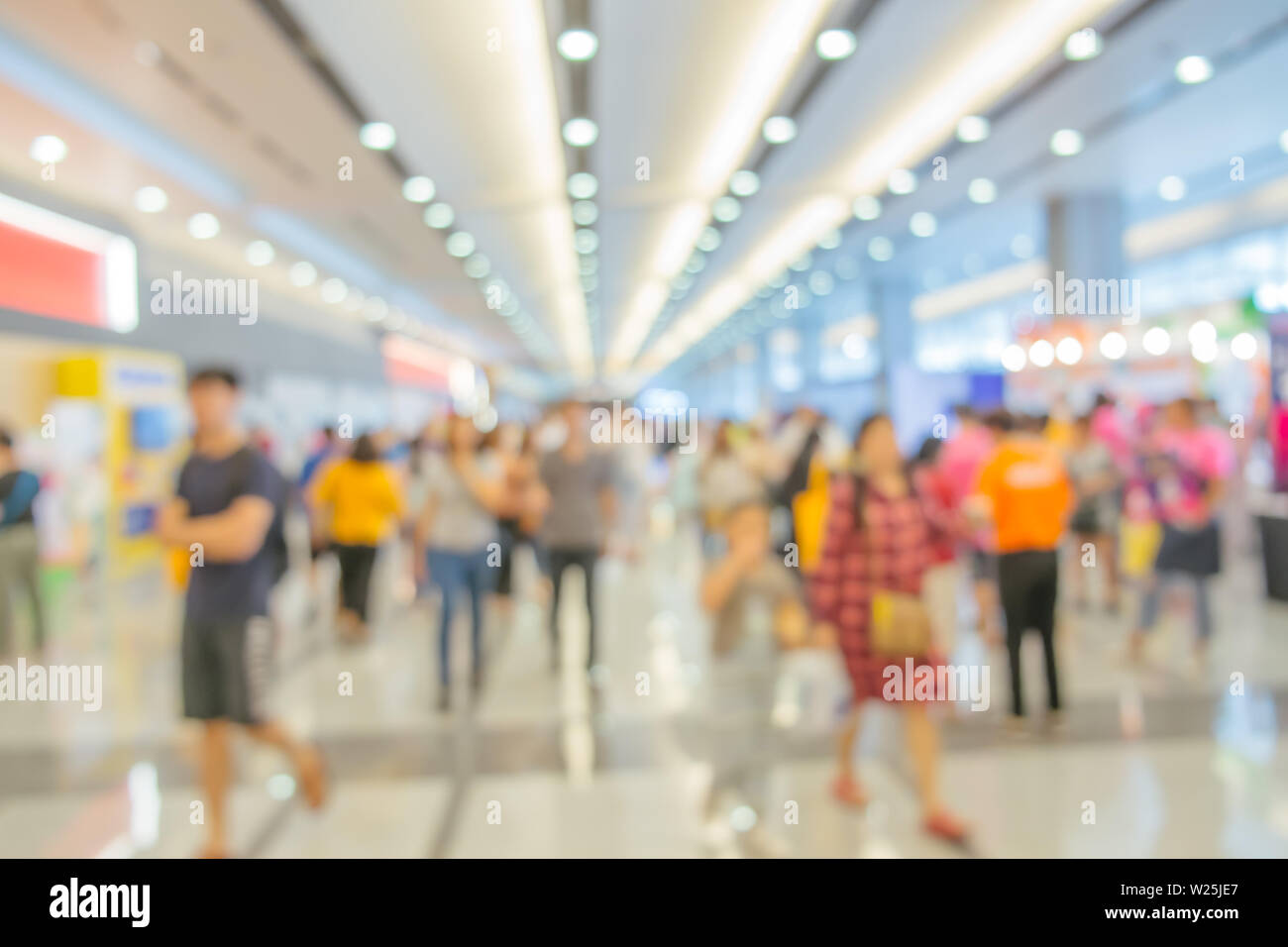 Abstract blurred background of people walking around modern interior building in the city. - Stock Image