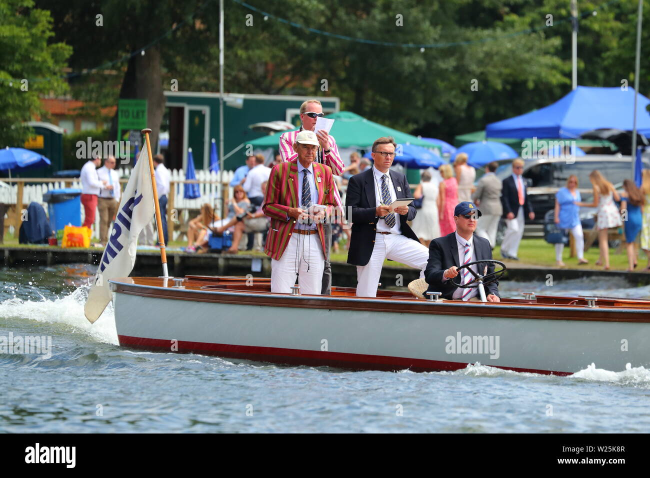 The Umpire boat follows the competitors at speed at Henley Royal Regatta, Henley-on-Thames, UK Stock Photo