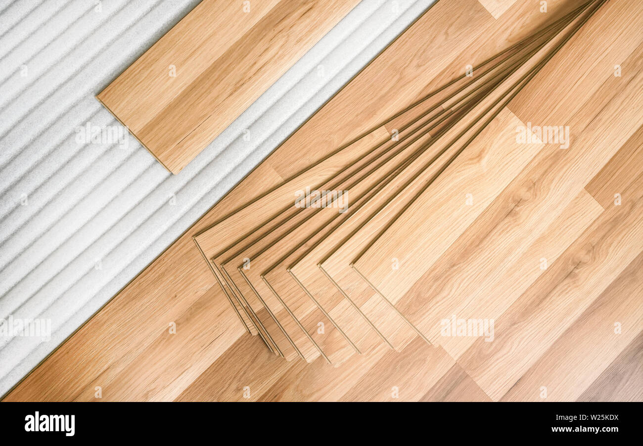 Tiles of laminated floor with wooden effect laying on white base foam, ready to be installed, top down view - home improvement background photo - Stock Image