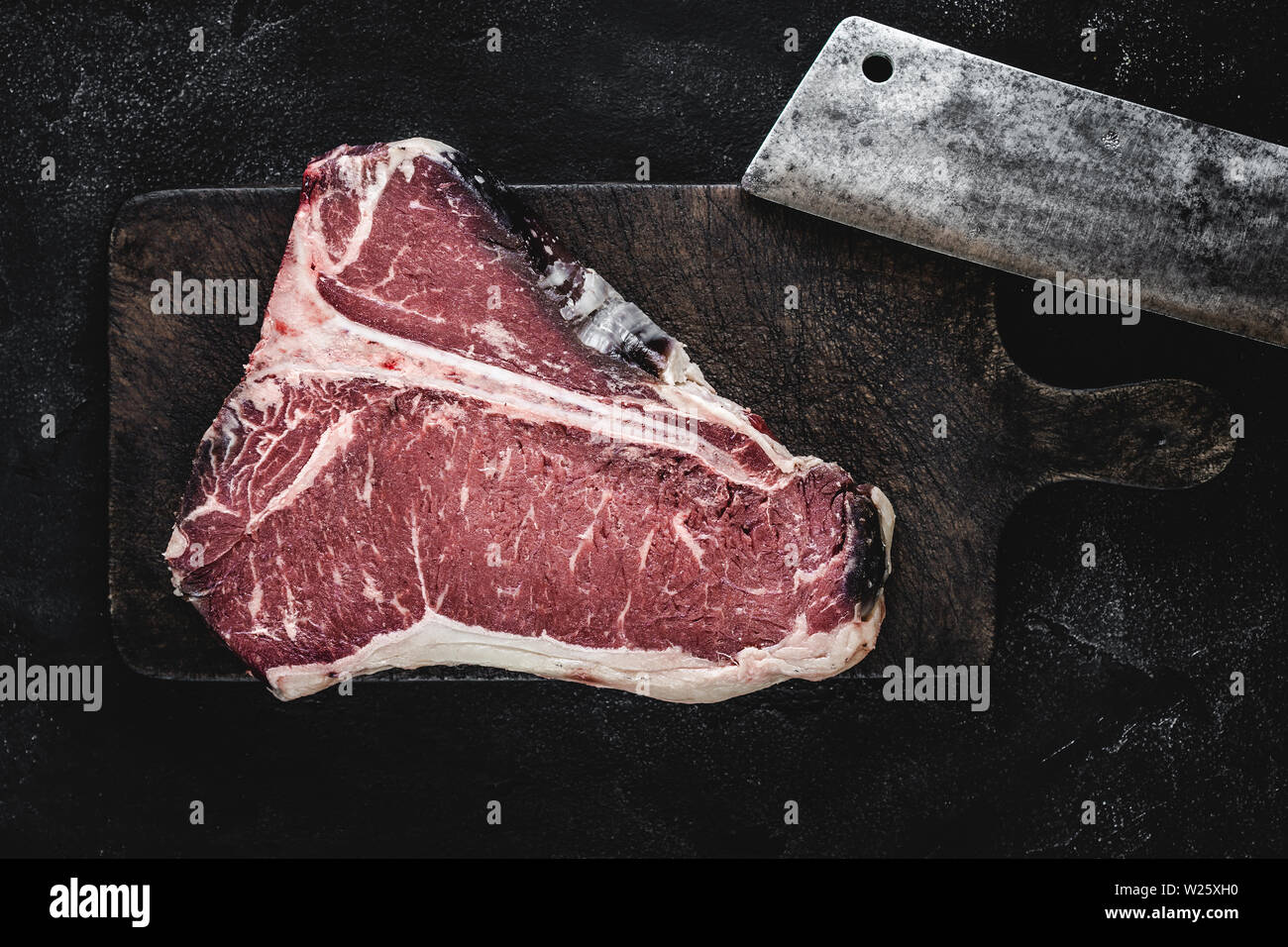 Prime Dry Aged Beef Raw T-bone Steak on Vintage Cutting Board Stock Photo
