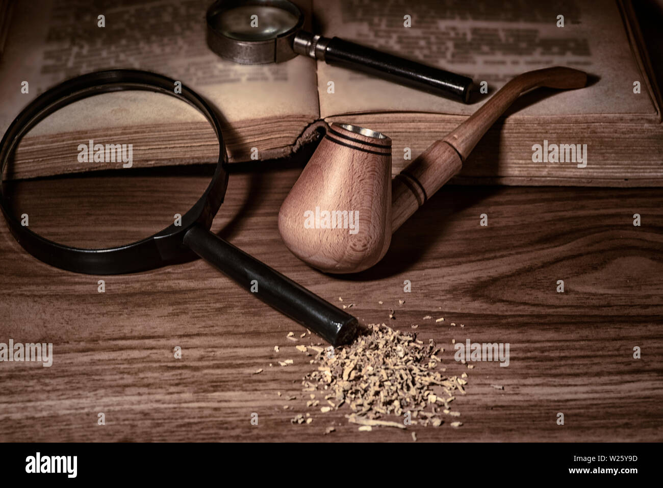 Smoking pipe with tobacco leaves on wooden background.wooden background.Wooden pipe with smoke on heap of chopped dried tobacco leaves against black b - Stock Image
