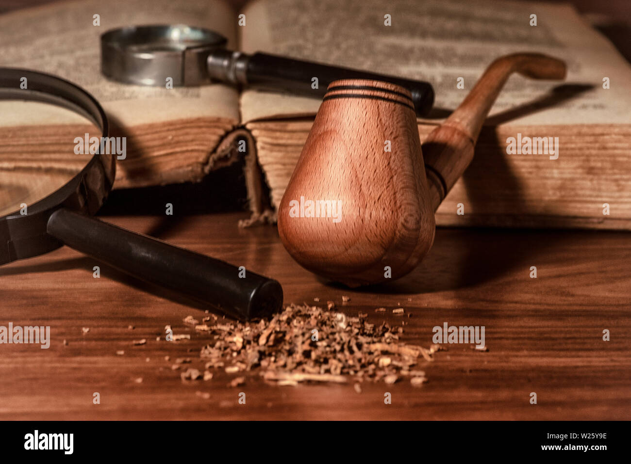 Wooden pipe with smoke on heap of chopped dried tobacco leaves against black background. - Stock Image