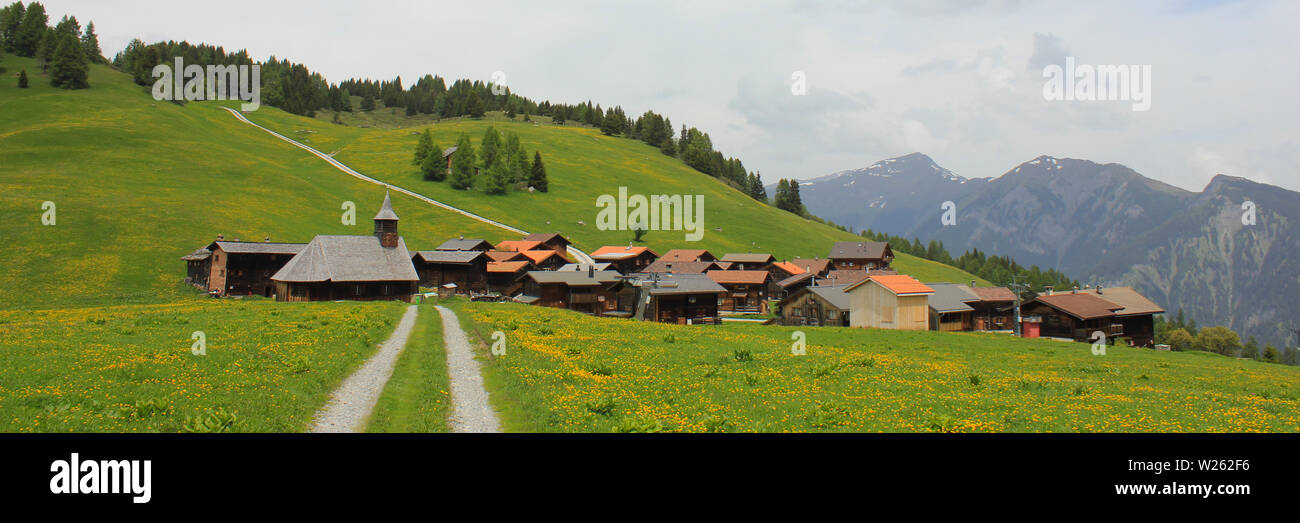 Timber church and chalets in Obermutten, Switzerland. - Stock Image