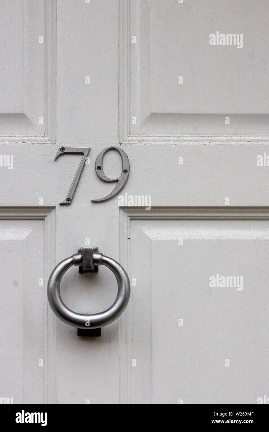 House number 79 with the seventy-nine in metal digits on a wooden front door - Stock Image