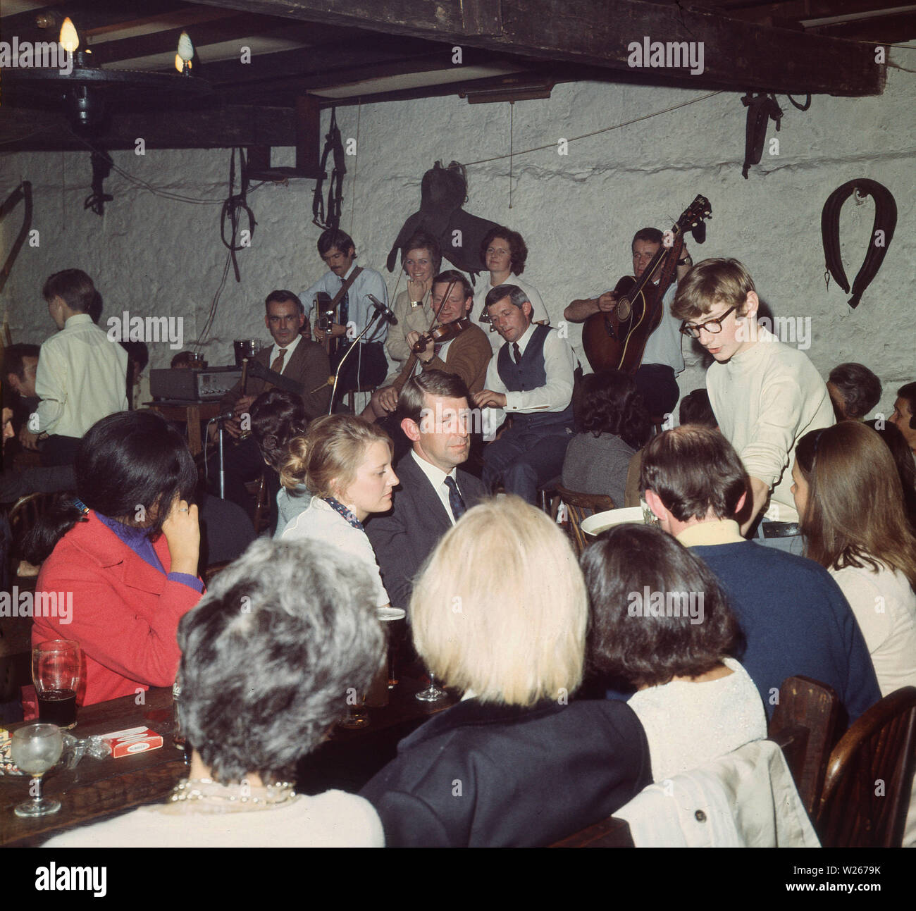 1960s, historical, In a Irish country pub, Ireland, people enjoying a drink and the music of a collective or group of musicans playing together on a small stage. - Stock Image