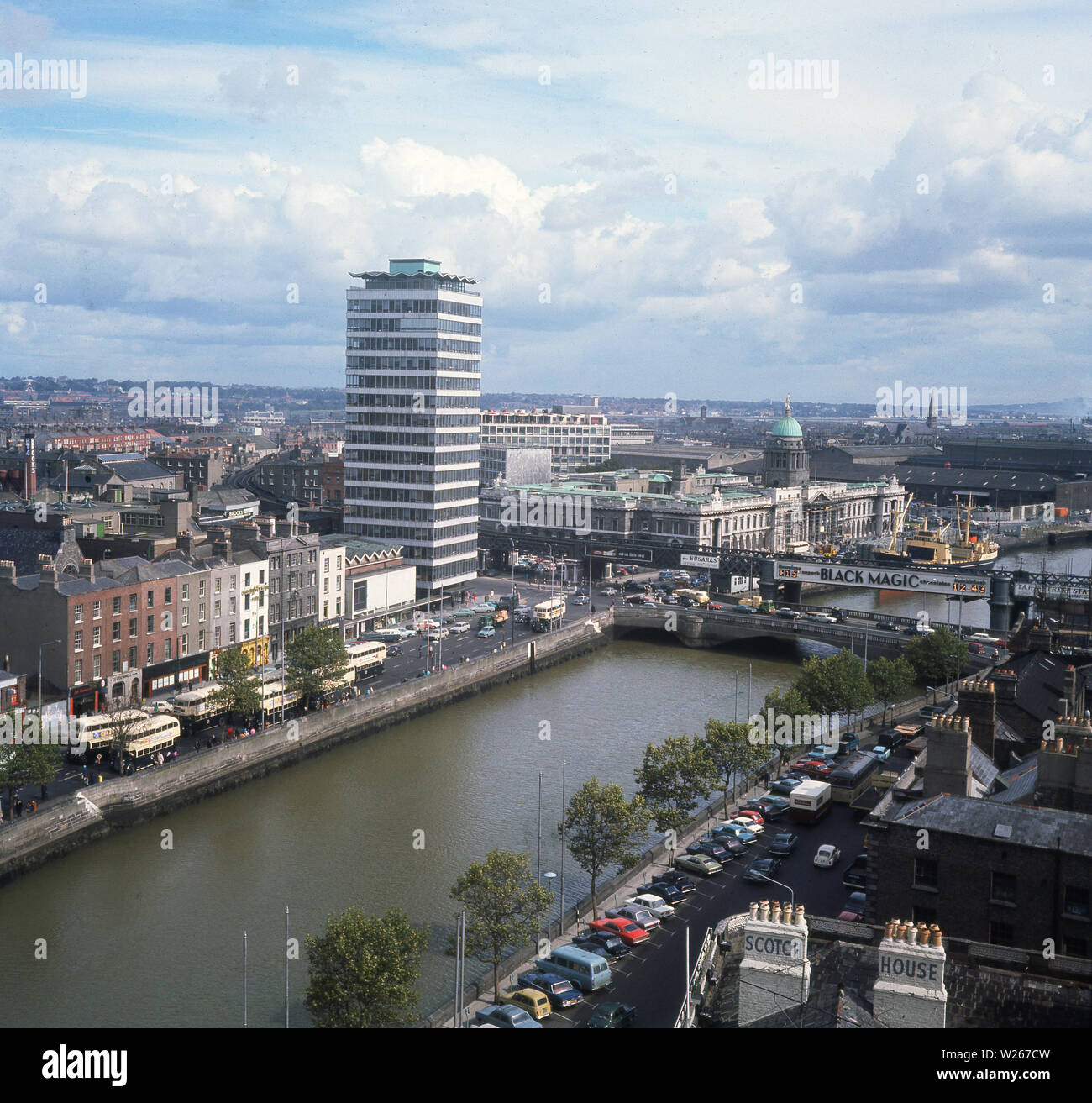 1960s, historical, a view over the skyline of Dublin, Ireland, showing traditional buildings and Liberty Hall, a high-rise modern office block, the river Liffey, the green dome of the Custom House, advertising billboards and double-decker buses. - Stock Image