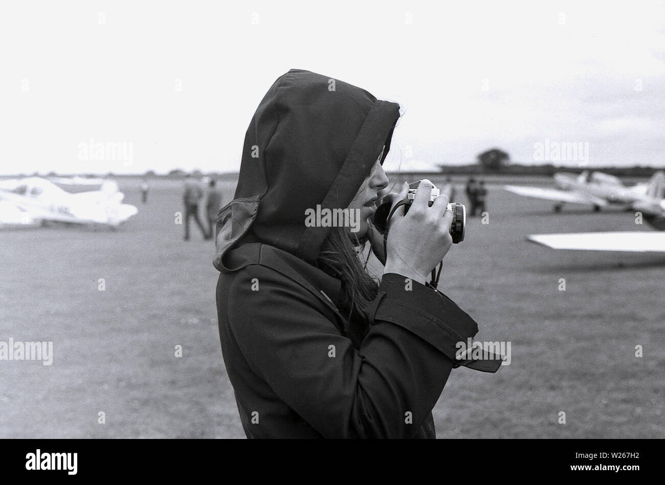 1970s, historical, a young women wearing a raincoat with its hood up over her hair, holding a film camera, taking photographs at an airshow, Old Warden Aerodrome, Biggleswade, England, UK. - Stock Image