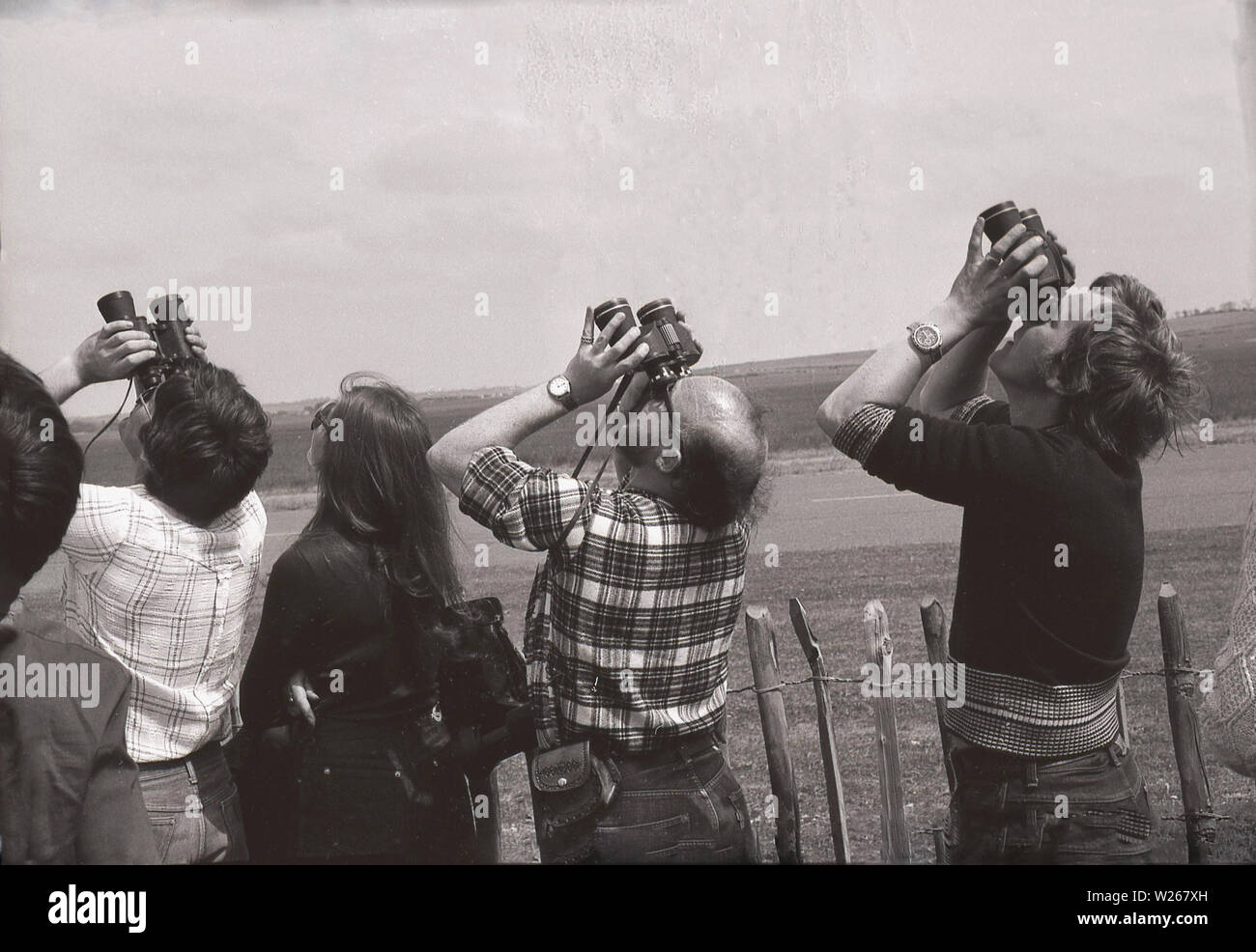 1970s, historical, spectators at an airshow standing behind a fence and using binoculars to look up in the distance, Old Warden Aerodrome, Biggleswade, England, UK. - Stock Image
