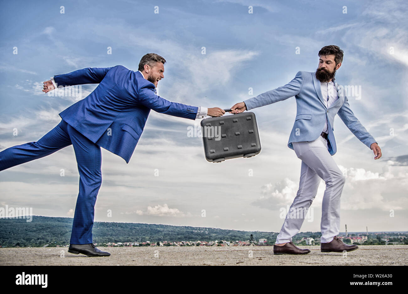 Men suits handover briefcase. Rascal racketeer extortionist cheating business transaction. Risky transaction. Fraud and extortion concept. Businessman takes away briefcase from business partner. - Stock Image