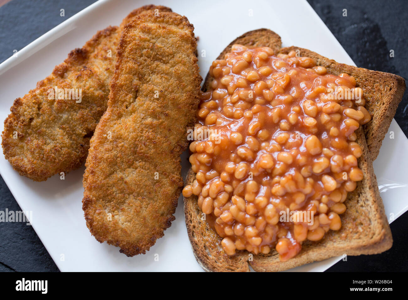 A meal of imported Alaskan breaded pollock fillets, Theragra chalcogramma, bought from a UK supermarket served with baked beans on toast. England UK G - Stock Image