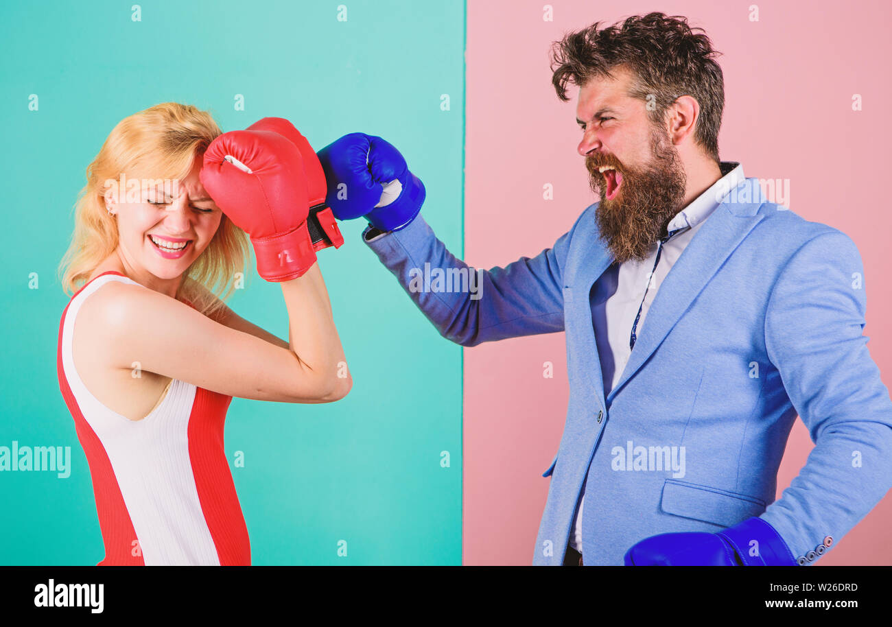Female and male boxers fighting in gloves. Domination concept. Gender battle. Gender equal rights. Gender equality. Man formal suit and athletic woman boxing fight. Couple in love competing in boxing. - Stock Image