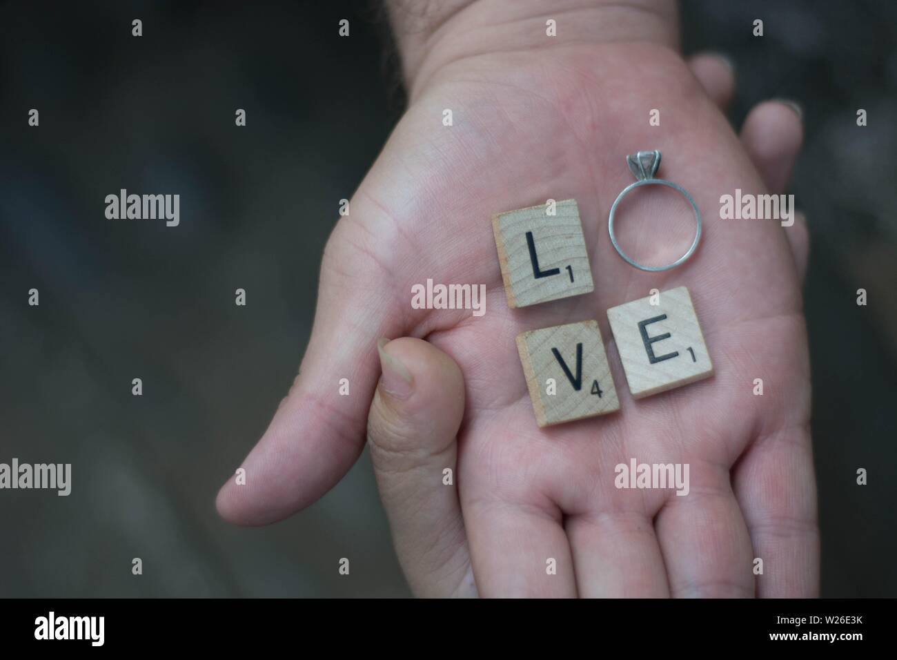Two lovers holding hands with letters and a ring spelling