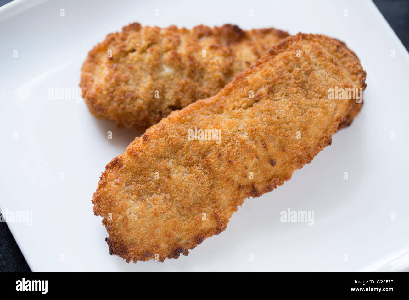 Two breaded Alaskan pollock fillets,Theragra chalcogramma, bought from a supermarket in the UK and served on a white plate. England UK GB - Stock Image