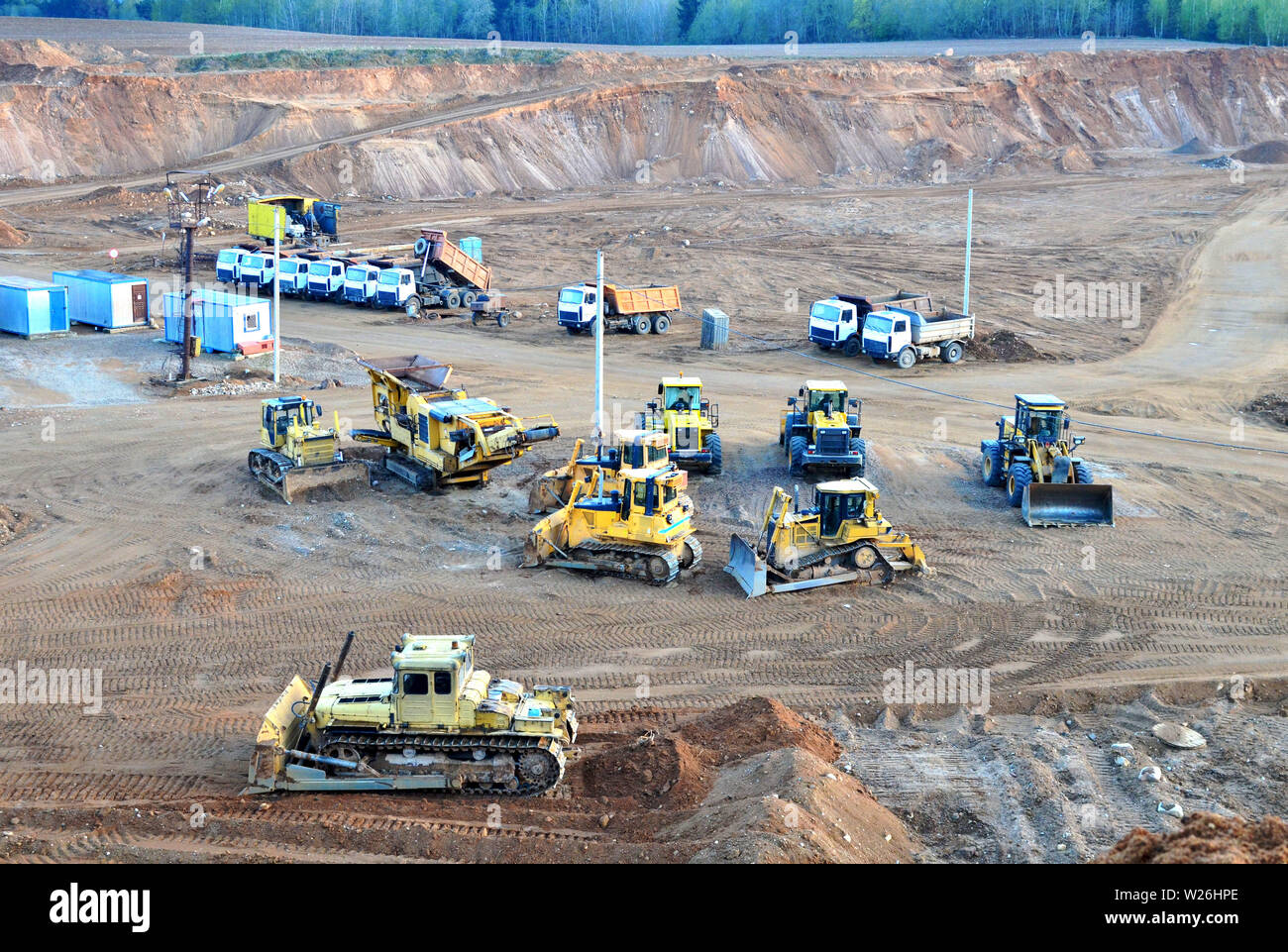 A lot of heavy construction equipment in the mining quarry. Parking with bulldozers, tractors, front loaders, excavators and dump trucks, top view - I - Stock Image