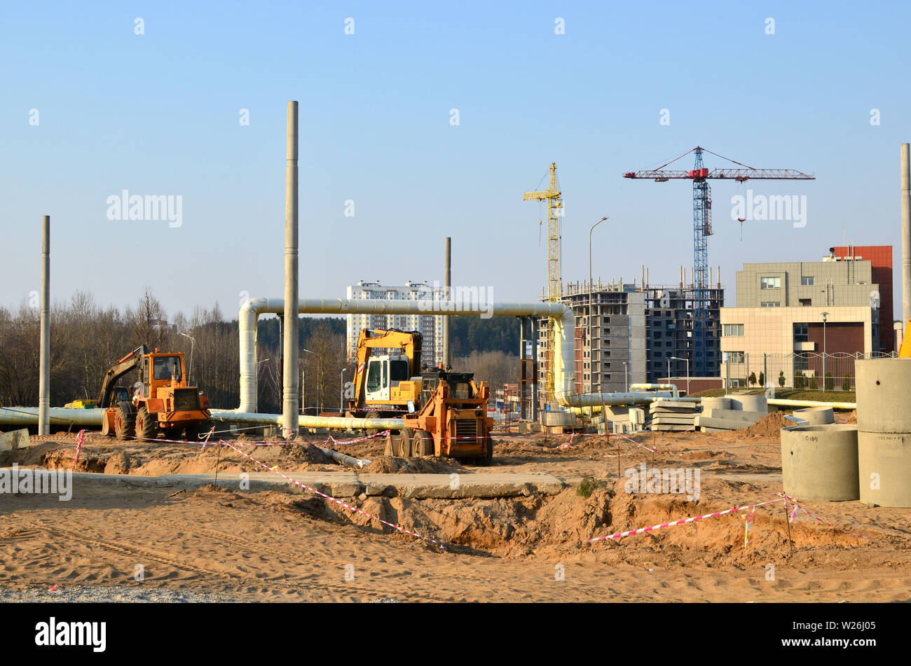 Heavy construction equipment and earthmoving excavators working on a construction site in the city. Laying or replacement of underground storm sewer p - Stock Image