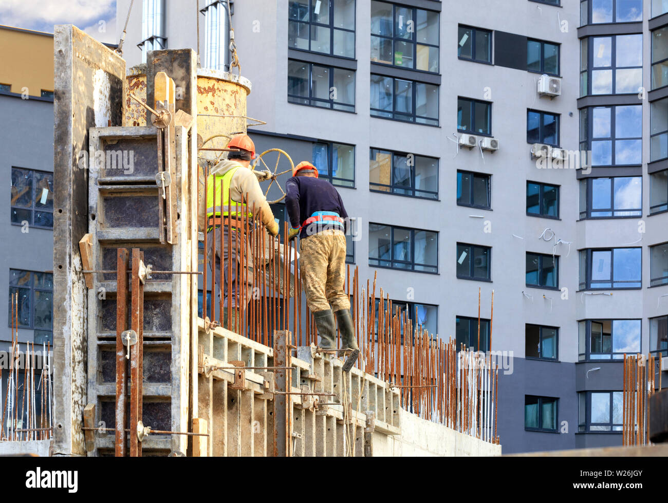 Workers poured concrete in the formwork of the walls on the construction of the new house against the background of a modern residential building. Stock Photo