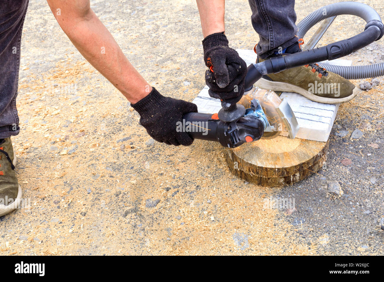 The worker uses a diamond cutting disc and an angle grinder to cut the paving bar and metal plate. - Stock Image