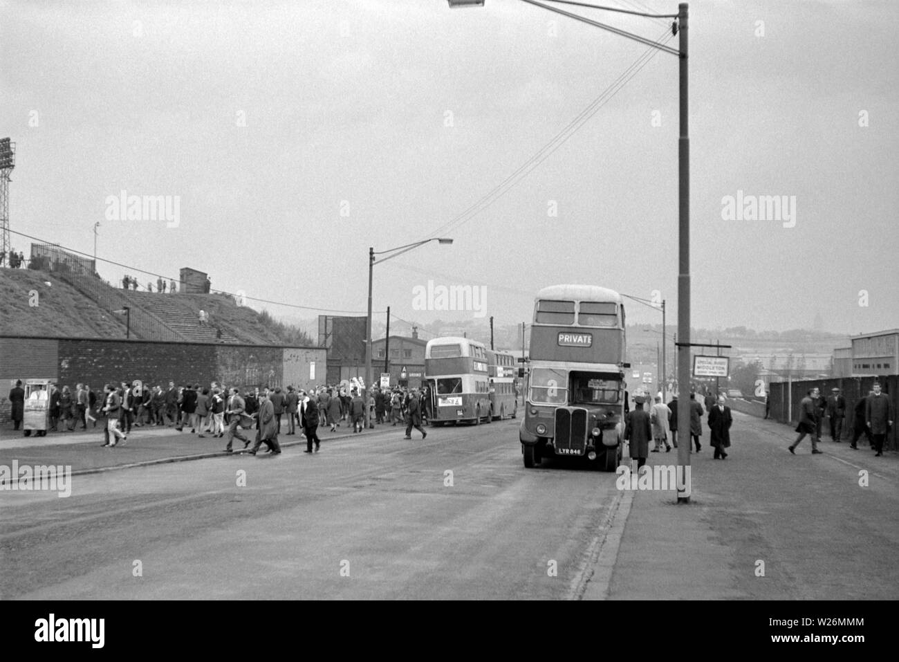 Match Day at Leeds United Football Ground. Probably taken during the 1960s, the image shows the home side fans getting of the busses to see their team in action. The main bus in the image is a Waymann Bodied AEC Regent III that would have been new in 1952 - Stock Image