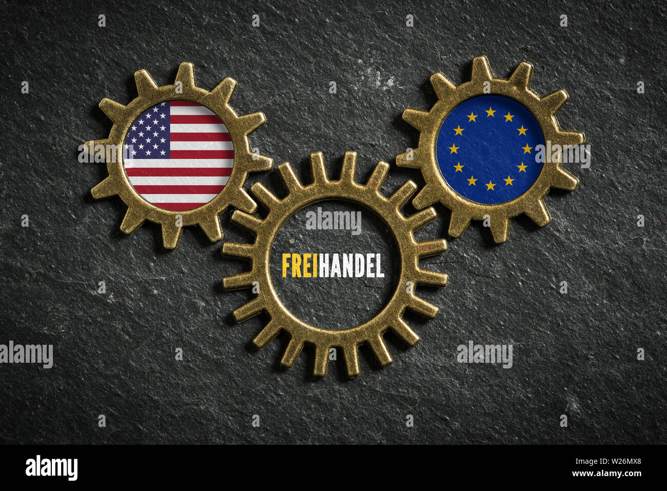 three cogwheels on slate background with the flags of USA and the EU and the word 'free trade' in German in the middle - Stock Image