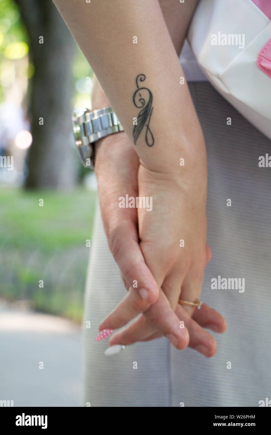 Closeup Of Male And Female Hand Holding Each Other On Girl S Hand Temporary Tattoo With Treble Clef Stock Photo Alamy