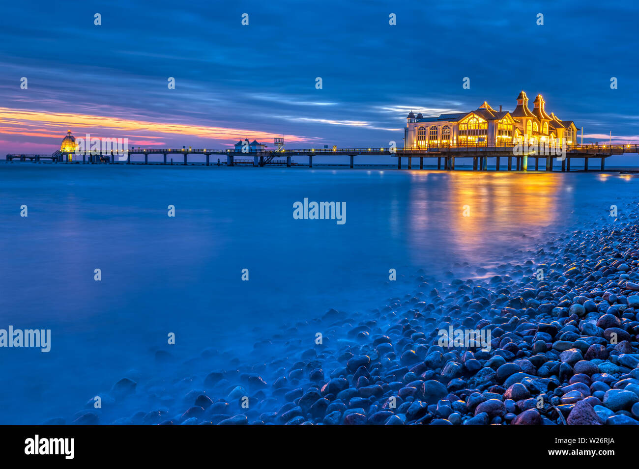 The sea pier of Sellin at night with pebbles in the foreground Stock Photo
