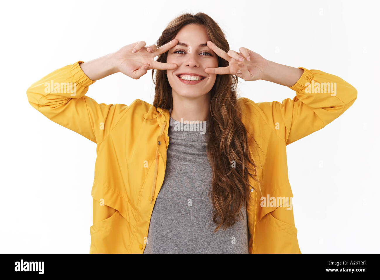 Positive minds healthy body. Bright lucky carefree gorgeous caucasian girl smiling broadly toothy grin show peace victory signs near eyes express upbe - Stock Image