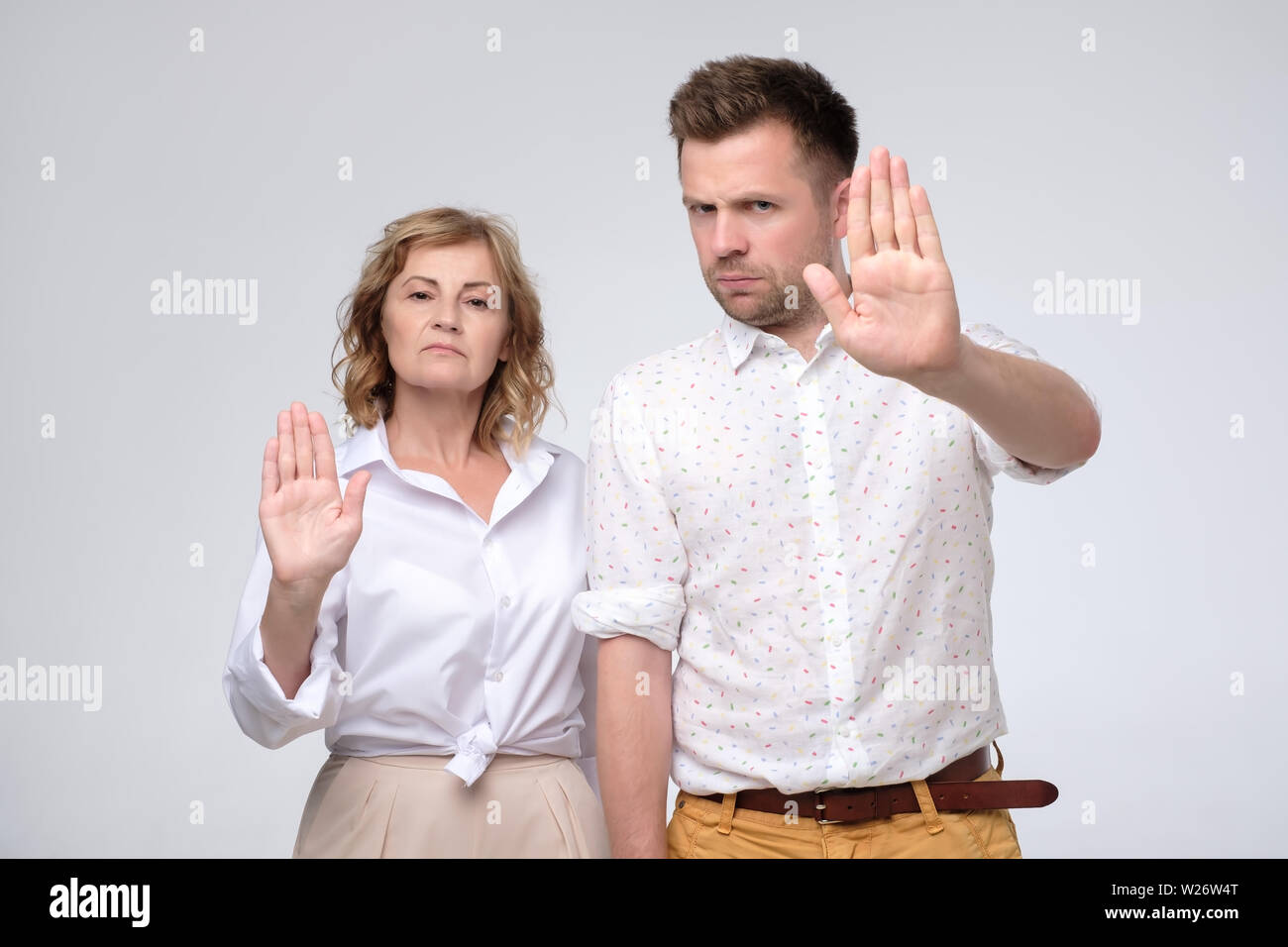Serious confident mature man and woman making stop gesture with outstretched arms, showing their disagreement or protest. We can not allow you to do i - Stock Image