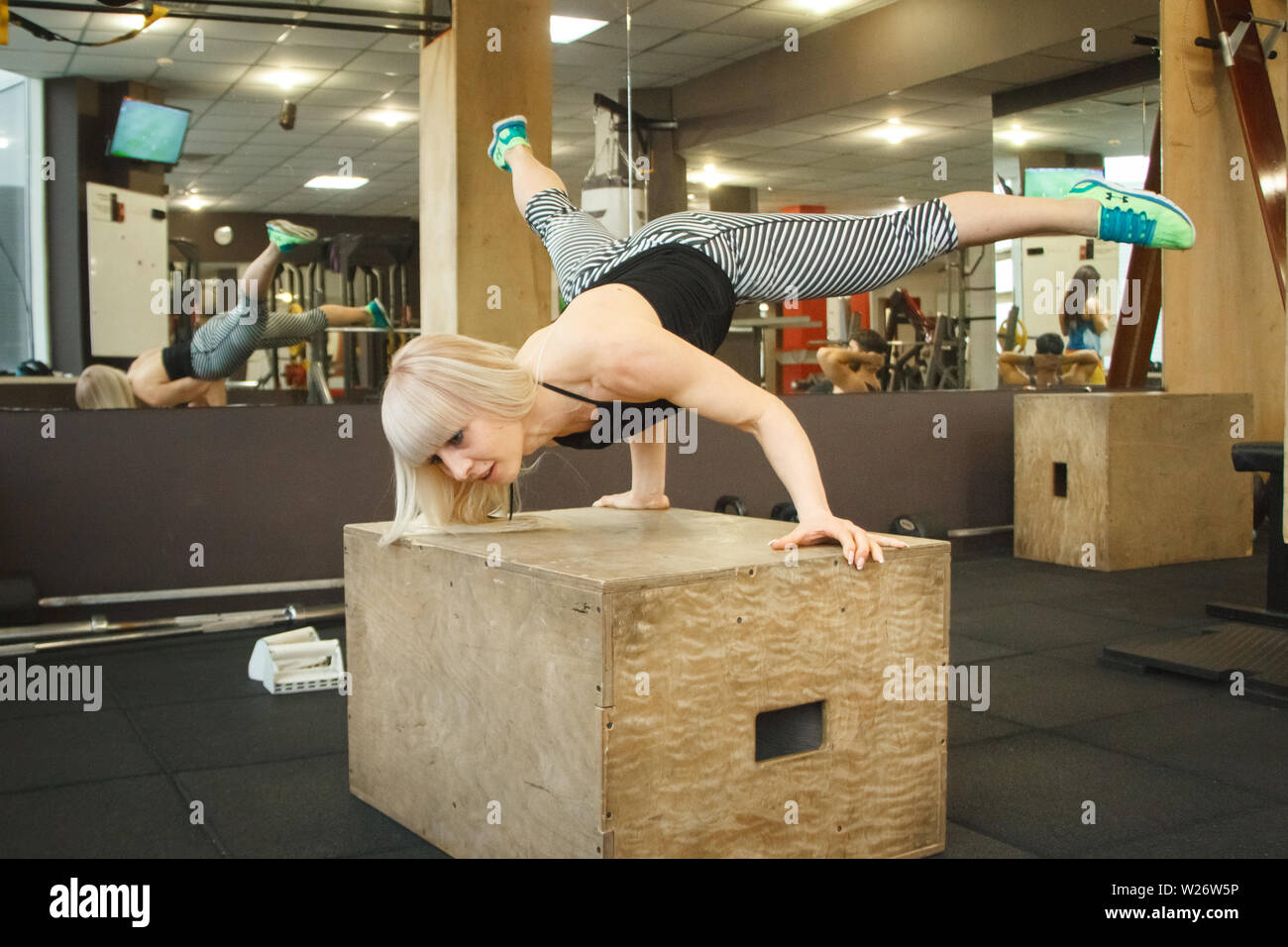 Young blonde female gymnast doing handstand in gym, copyspace - Stock Image