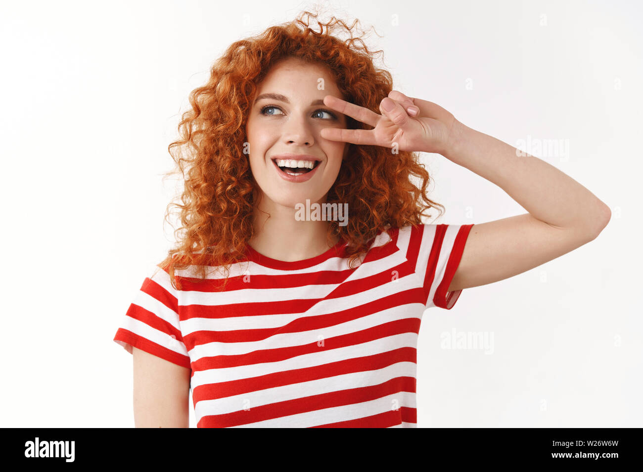 Close-up carefree joyful redhead curly woman blue eyes having fun enjoy vacation relaxing showing peace victory gesture lucky win summer travel journe - Stock Image