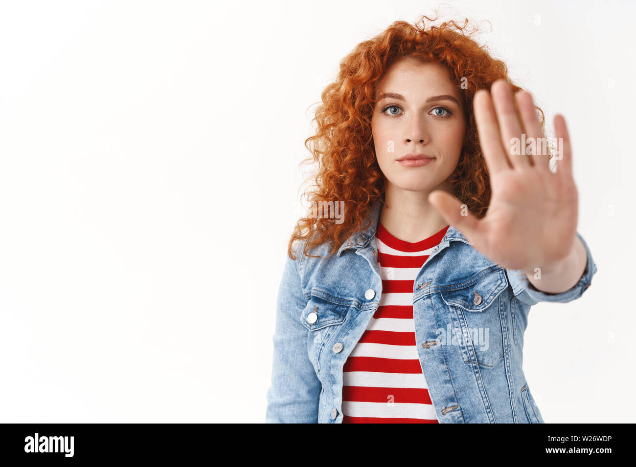 Close-up serious-looking persuasive redhead attractive female model demand stop hold on extend palm camera taboo enough gesture give restriction ban b Stock Photo