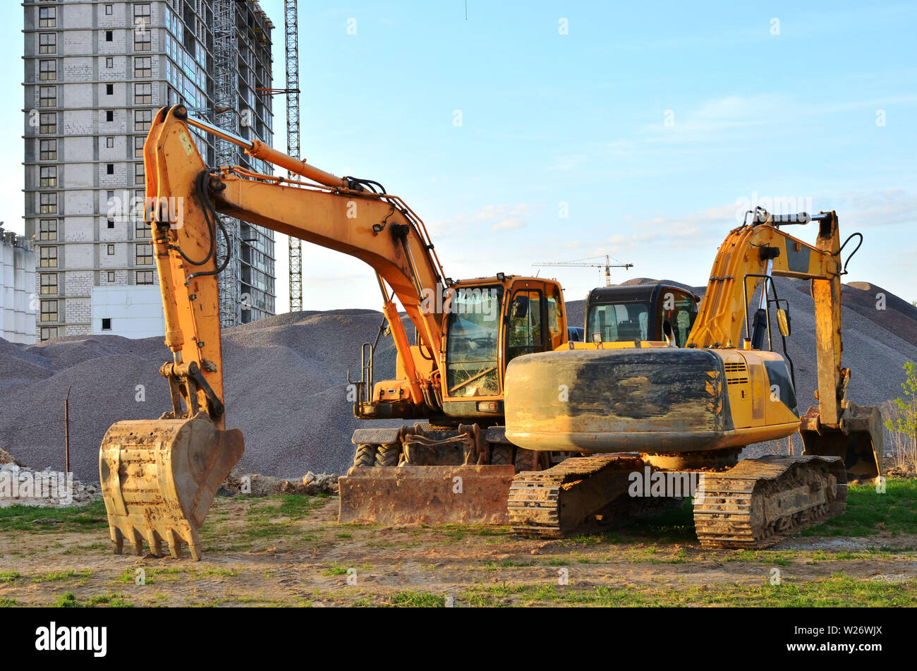 Wheel and tracked heavy excavators working at construction site. hydraulic excavator crane at building site on sunny day - Image - Stock Image
