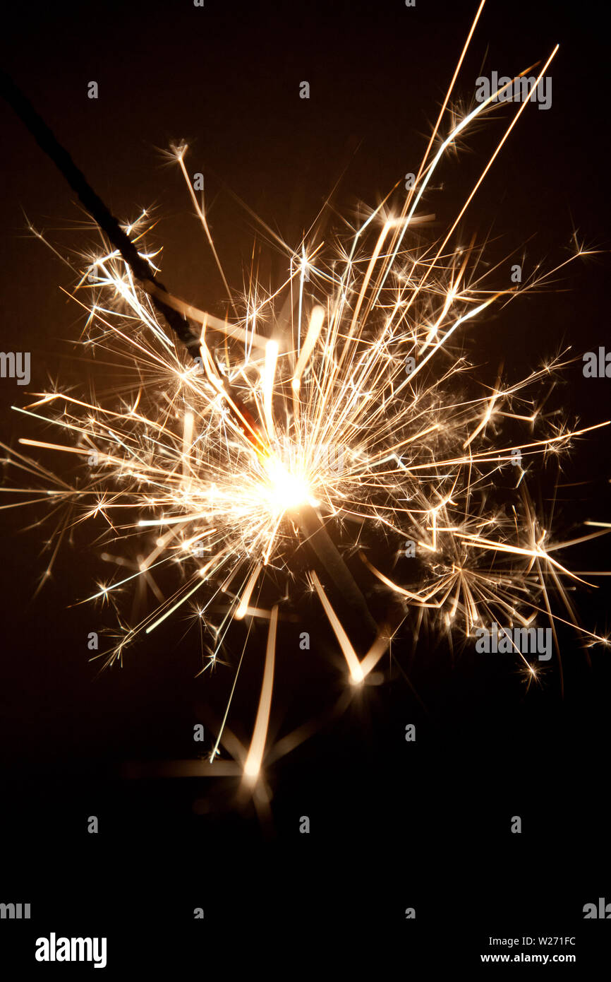Sparkler in the night with lots of sparks. - Stock Image