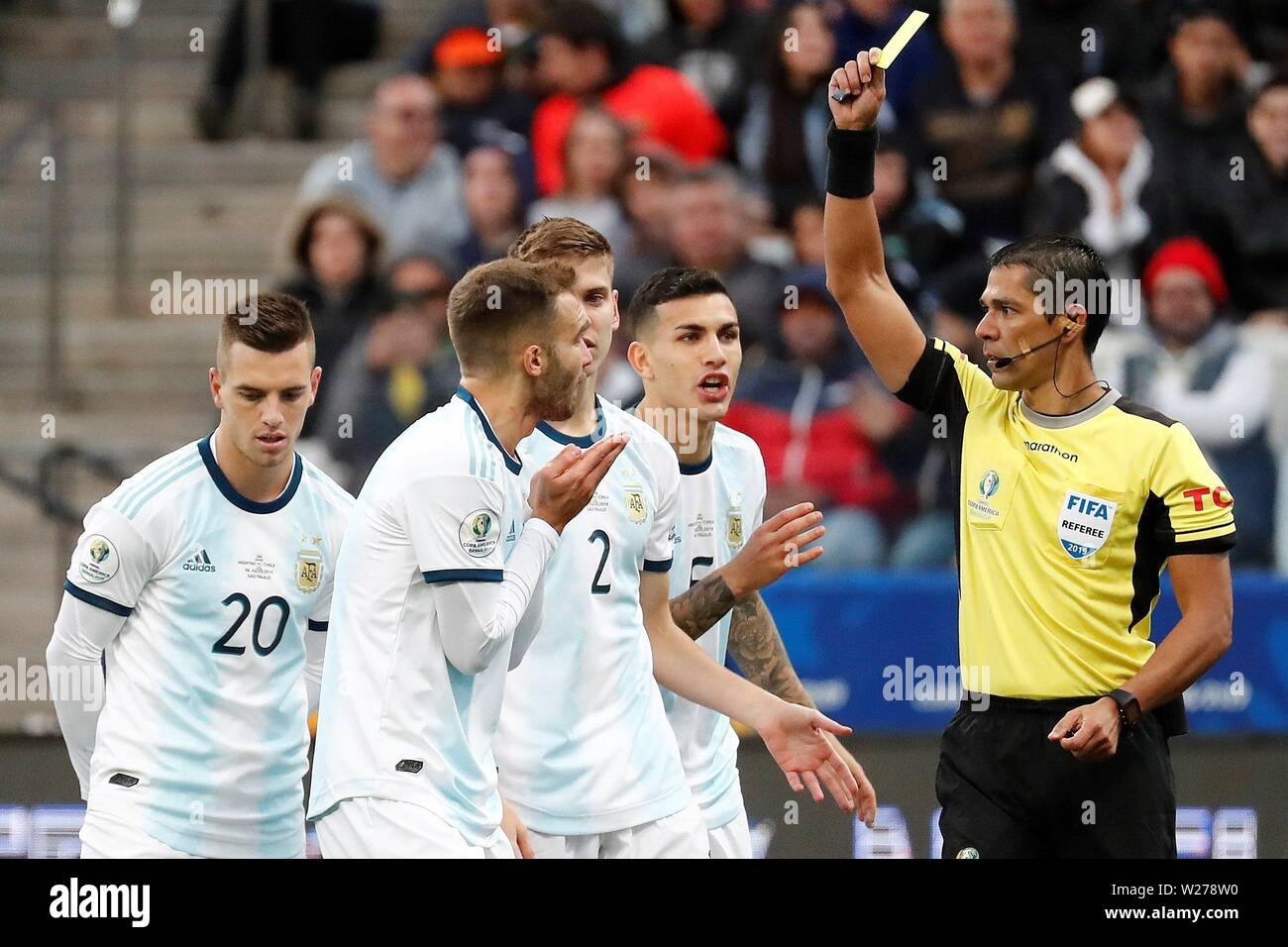 Sao Paulo, Brazil. 06th July, 2019. Argentinian players argue with the referee as he shows a yellow card, during the Copa America 2019 3rd place soccer match between Argentina and Chile, at Arena Corinthians Stadium in Sao Paulo, Brazil, 6 July 2019. Credit: Sebastiao Moreira/EFE/Alamy Live News - Stock Image