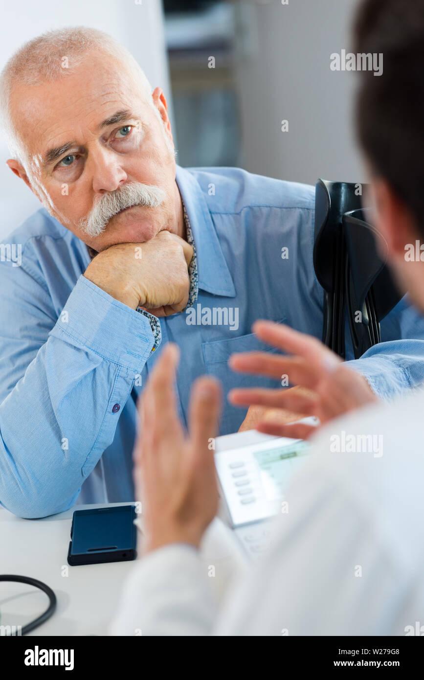 doctor talking to senior man - Stock Image