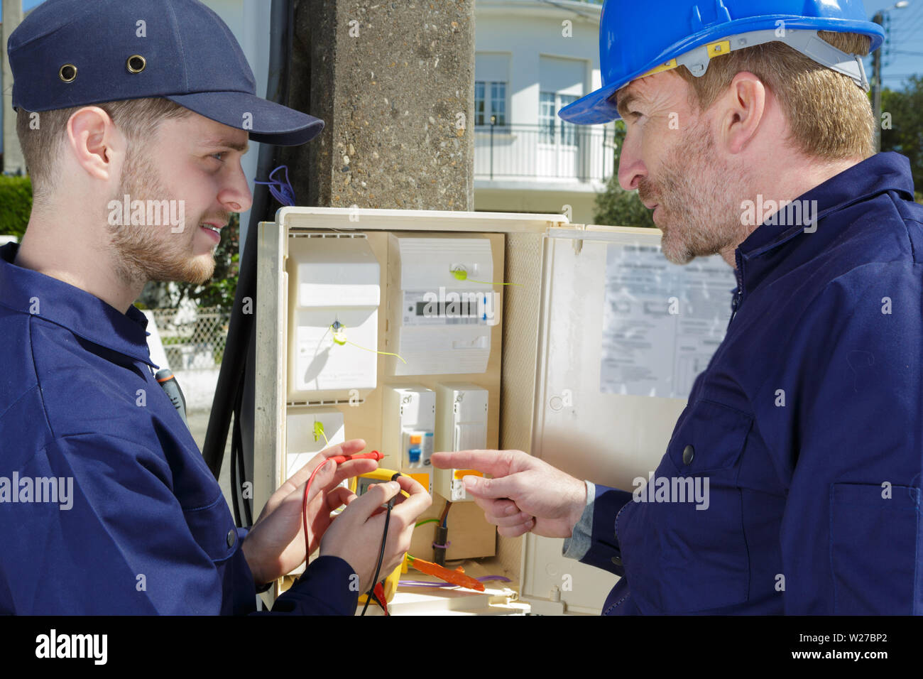 electrician opening an outdoor fuse box Stock Photo