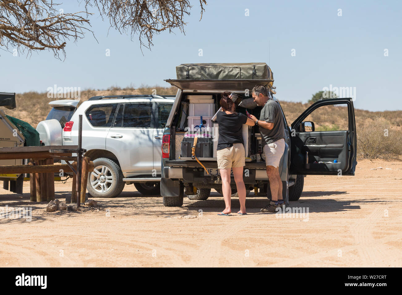 Couple Or Man And Woman Unpacking Their 4x4 Camping Off Road Overland Vehicle At A Camp Site Picnic Area In Kgalagadi Transfrontier Park South Africa Stock Photo Alamy