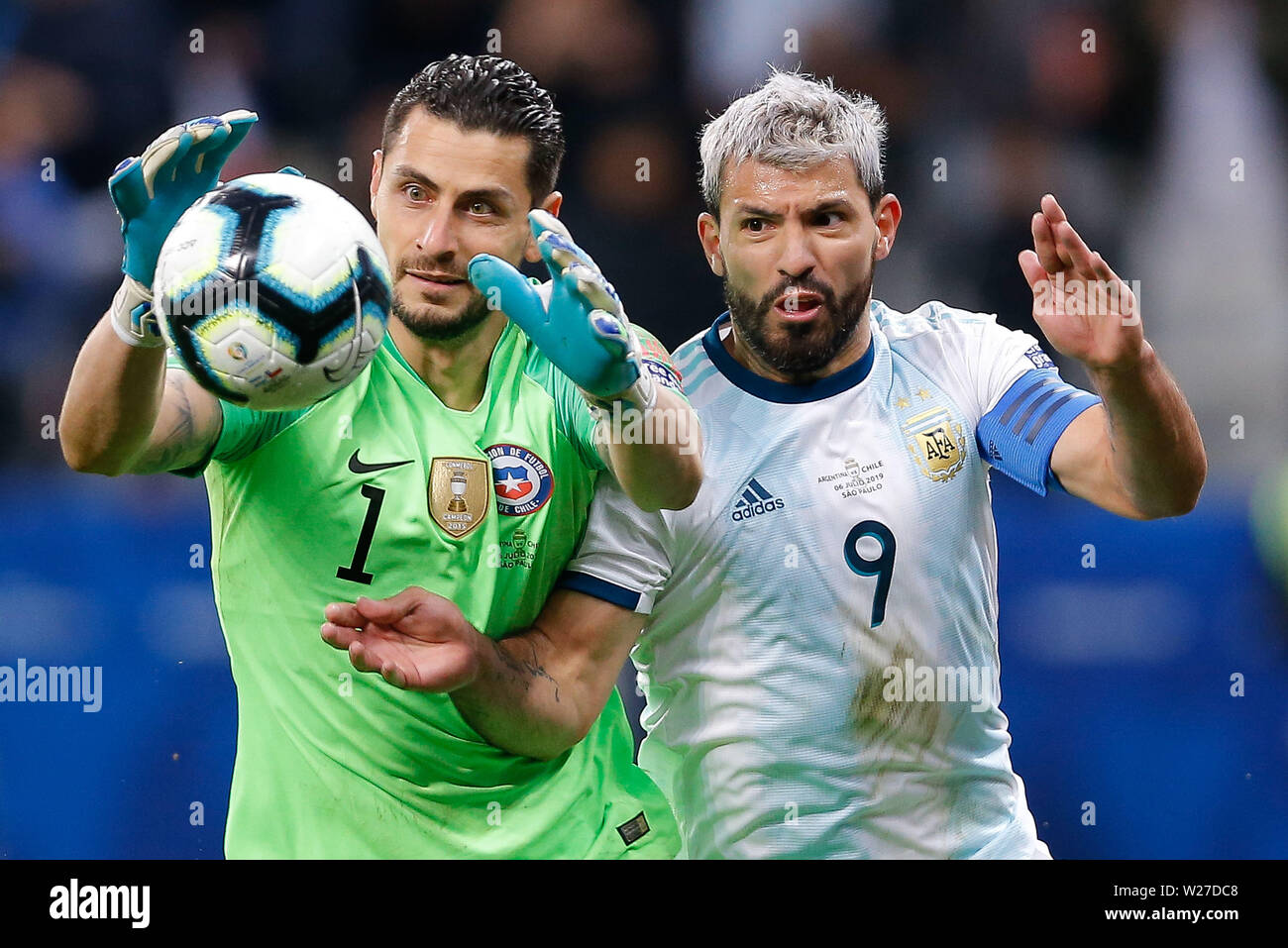 SÃO PAULO, SP - 06.07.2019: ARGENTINA VS. CHILE - Gabriel Arias of Chile plays the ball with Sergio Kun Aguero of Argentina during a match between Argentina and Chile, valid for the third place match of the Copa América 2019, held this Saturday (06) at the Corinthians Arena in São Paulo, SP. (Photo: Marcelo Machado de Melo/Fotoarena) - Stock Image