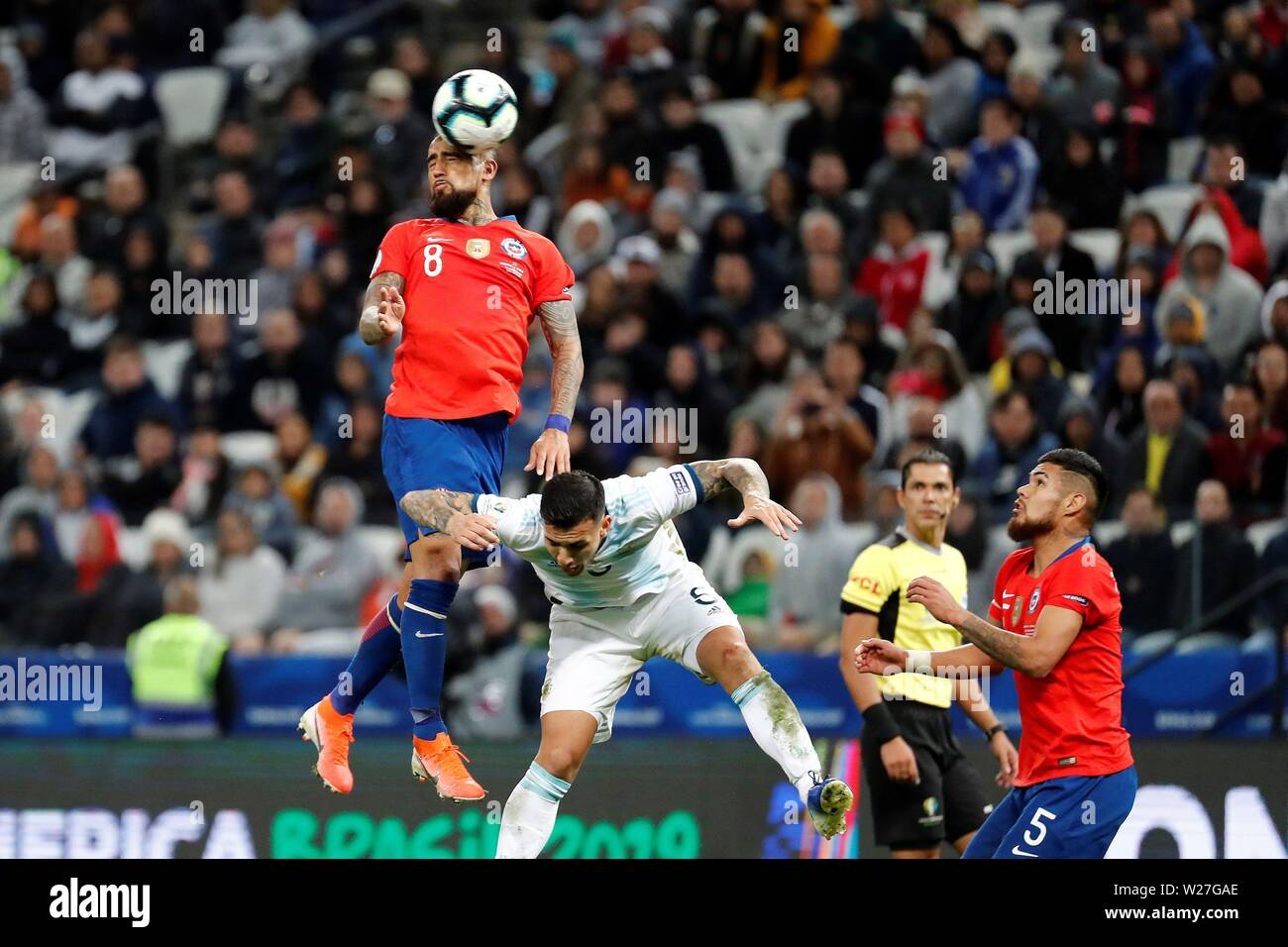 Sao Paulo, Brazil. 06th July, 2019. Chilean Arturo Vidal (L) vies for the ball with Argentinian Leandro Paredes, during the Copa America 2019 3rd place soccer match between Argentina and Chile, at Arena Corinthians Stadium in Sao Paulo, Brazil, 6 July 2019. Credit: Sebastiao Moreira/EFE/Alamy Live News - Stock Image
